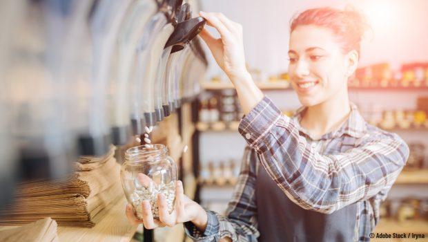 Photo d'une jeune femme qui remplit un bocal en verre de haricots blancs au sein d'une épicerie spécialisée dans le vrac.